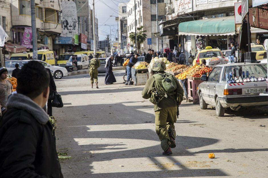 militari corrono sulla strada del mercato ad Hebron