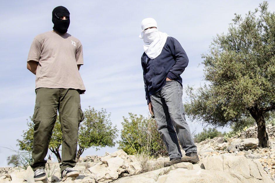 ragazzi palestinesi manifestano davanti alla Barriera
