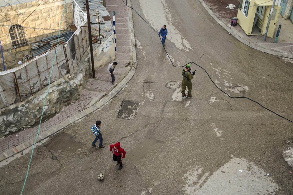 militari e bambini che giocano a pallone in strada ad Hebron